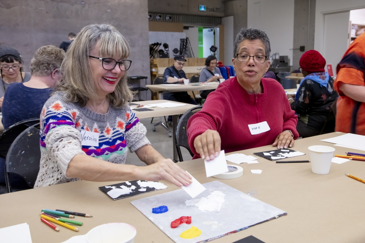 Two women paint using a new technique during the AGO Seniors Social