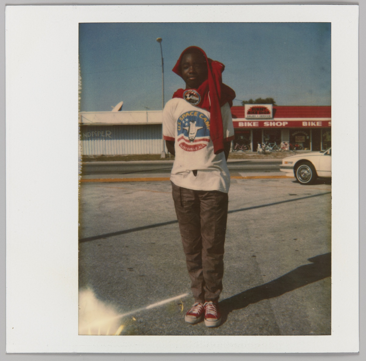 Zun Lee. Boy standing in parking lot with red sweater wrapped on his head