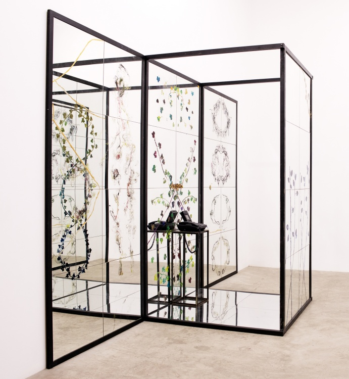 A structure of clear glass panels is decorated with flowers and other greenery.