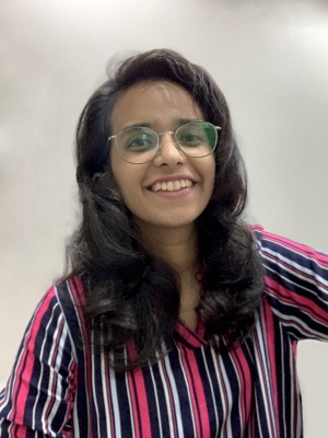 Shivani is pictured in this photo. She smiles, staring into the camera. She wears a vertical stripe shirt with pink, blue and white lines. She is pictured with long brown curly hair and thin wireframe glasses.