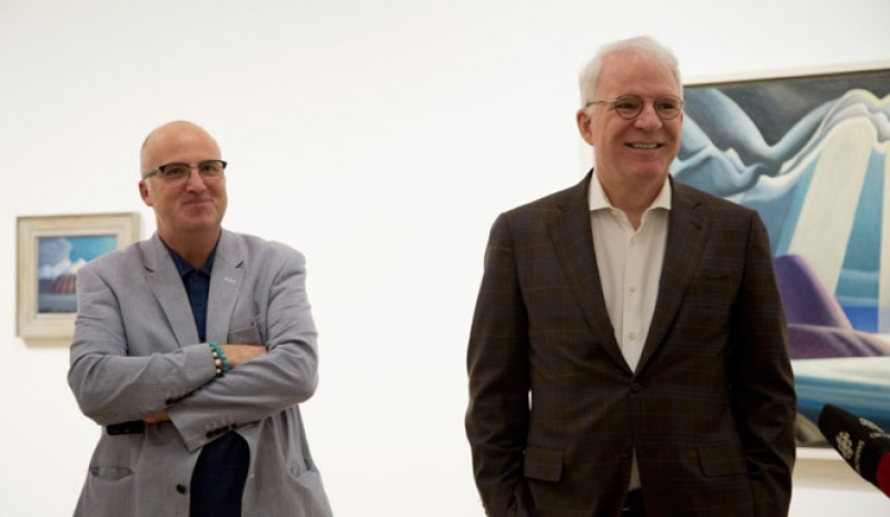 Andrew Hunter and Steve Martin in front of paintings in gallery