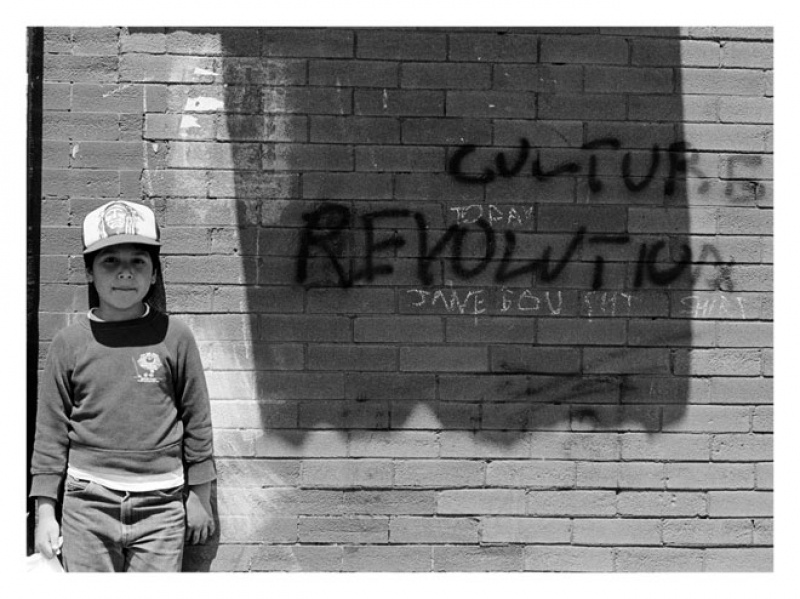 a boy standing near a brick wall with graffiti