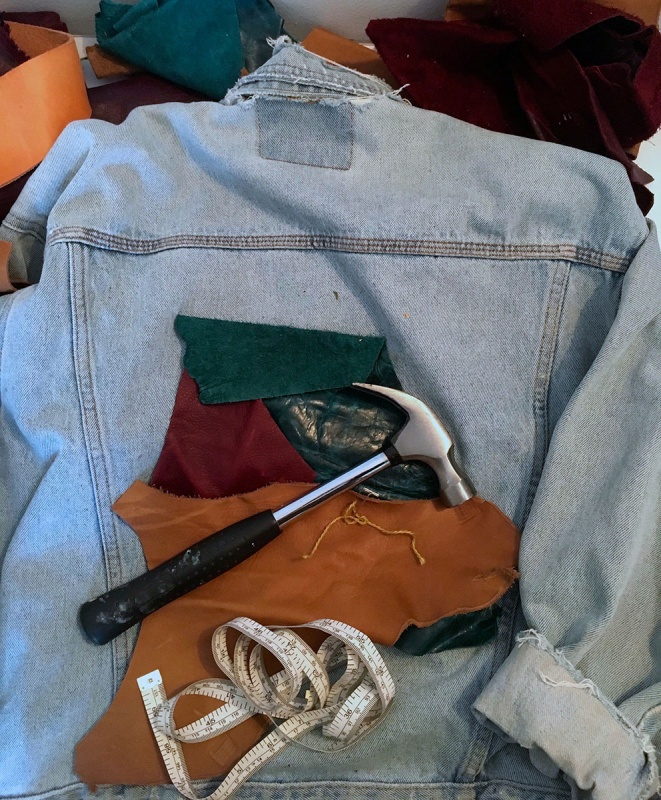 Leather pieces on jean jacket with hammer and measuring tape