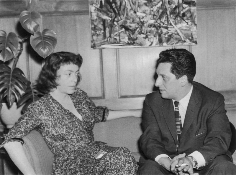 image of artists Joan MItchel and Jean-Paul Riopelle seated on a sofa in front of Riopelle's paintings
