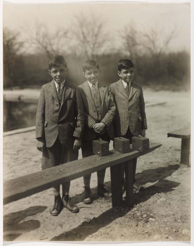 black and white photo of triplets dressed in suits standing behind a bench outdoors