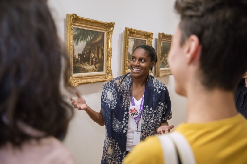 volunteer in front of painting with visitors giving a themed tour