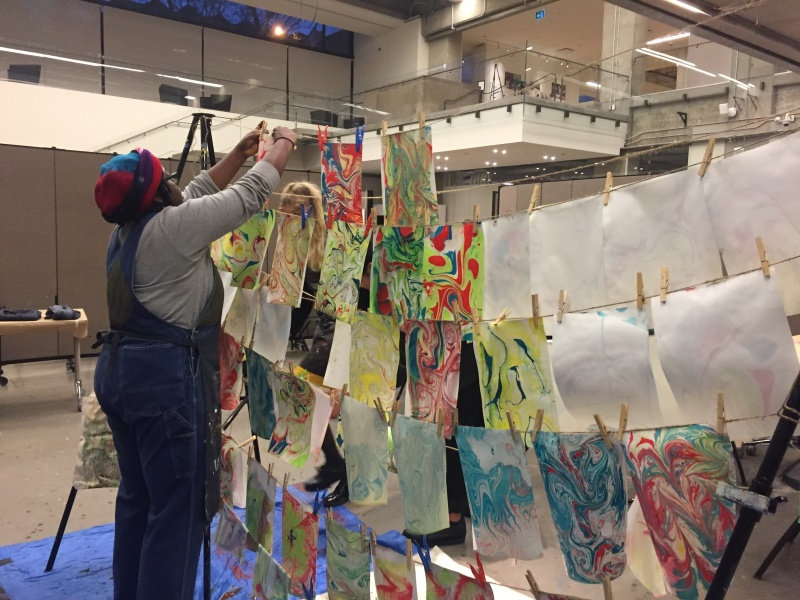 instructor hanging paper marbling projects on clothesline to dry