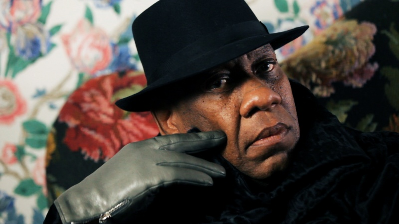 image of Andre Leon Talley in a hat in front of floral wallpaper