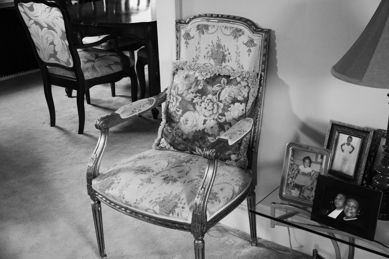 black and white image of a upholstered chair beside a table with framed family photos