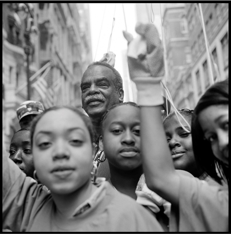 black and white photo of writer Edouard Glissant on a city street with young people in foreground