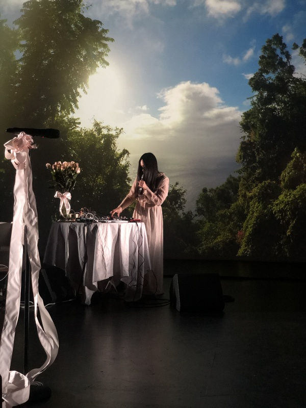 colour photo of performance featuring Miho Hatori in front of a green treed landscape, with a table draped in white with pink ribbons