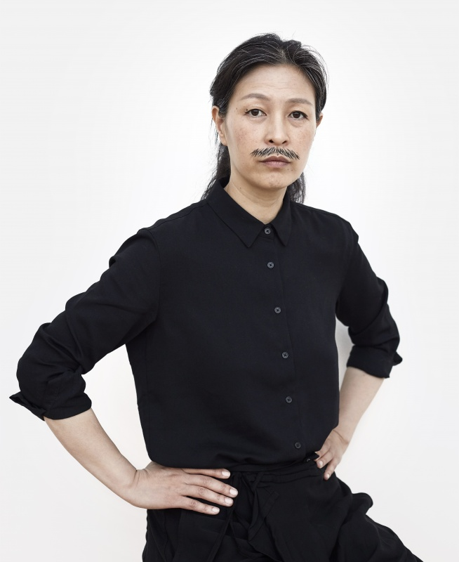Artist Haeugue Yang poses with hands on hips, sporting a drawn on mustache