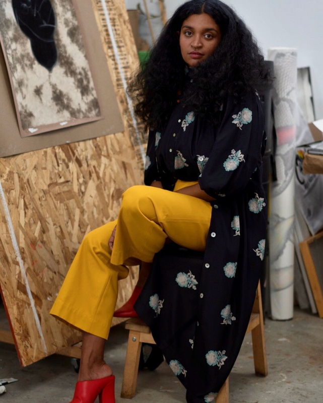 Artist Rajni Perera seated in her studio wearing a long black coat and yellow trousers