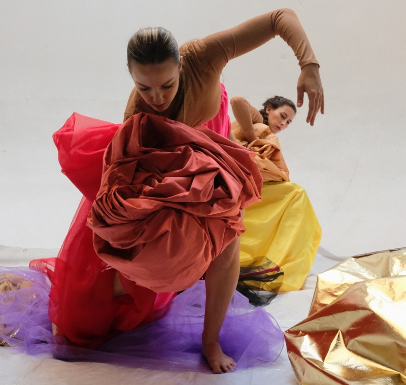 Image of two dancers wrapped in brightly colored cloth.