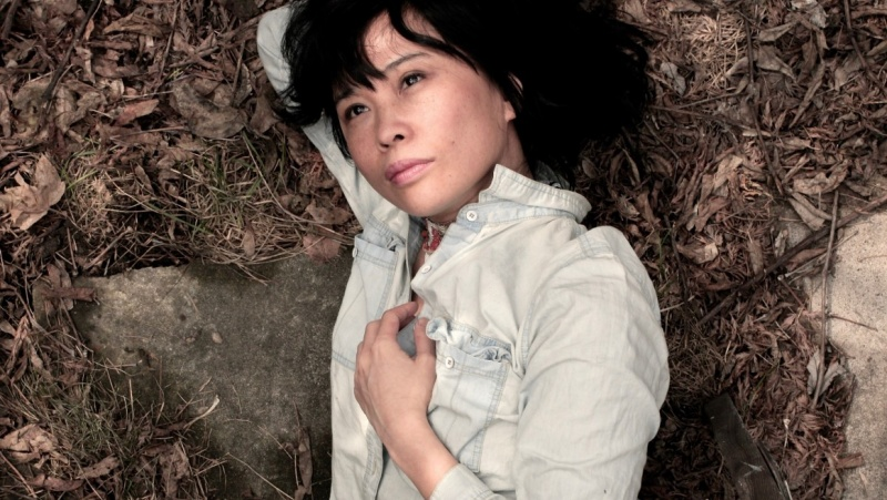 Figure dressed in a white shirt lays on the ground. One hand is place over their chest.