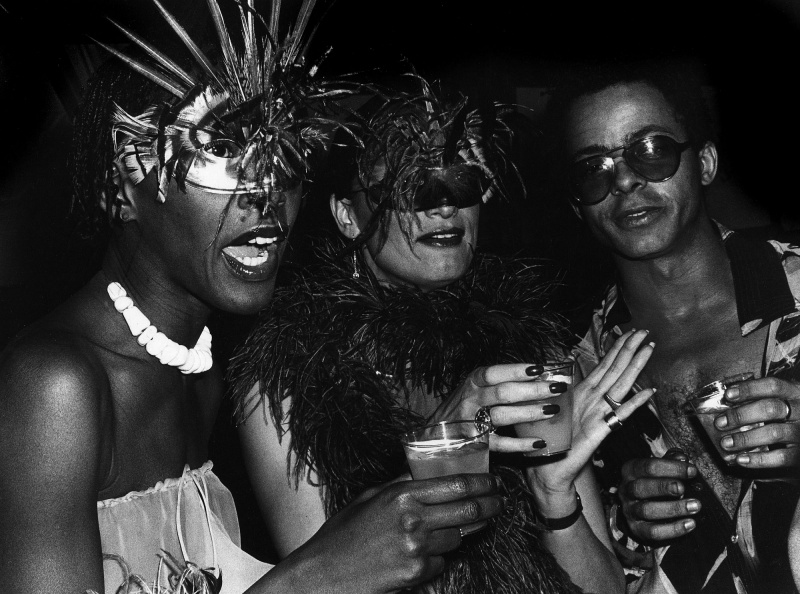Three figures are pictured in this black and white scene. The figure on the far left wears a metallic costume mask with feathers which protrude upwards. Their mouth is open as they hold a glass in their hand. The figure in the middle wears a dark feather boa, presents a half-smirk and a feather black costumer mask. They are also holding a glass with an opaque liquid. The figure on the far right has short hair and wears a buttoned shirt that has been unbuttoned. They stare into the camera wearing sunglasses.