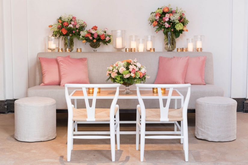 table with sofa and chairs, floral arrangements, candles