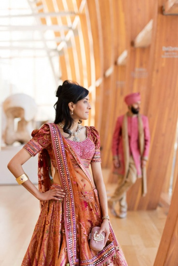 bride wearing sari looking out window in Galleria Italia, groom in background
