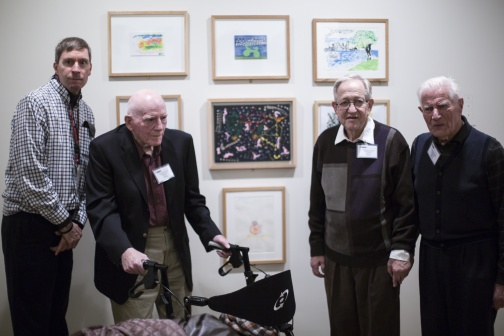 elderly visitors with walker in front of art works