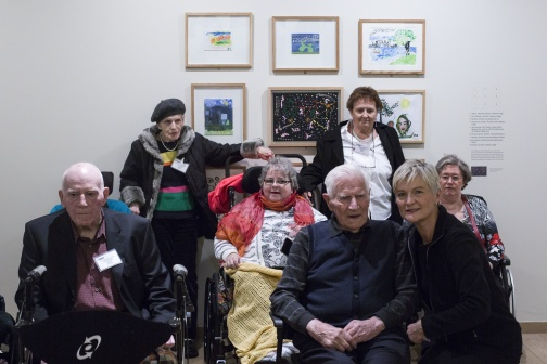visitors in wheelchairs with caregivers in front of art works