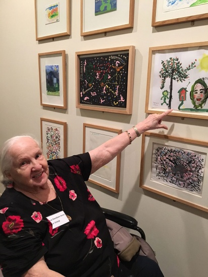 elderly visitor in wheelchair pointing at art work