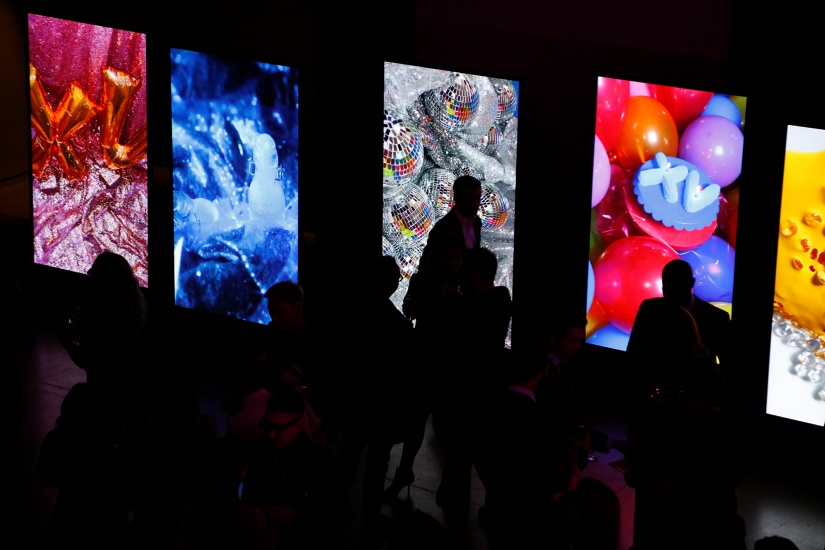 Group of people in front of screens with digital photographs displayed