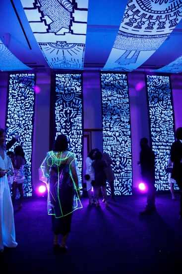 Glowing canvas banners and a woman in a plastic coat